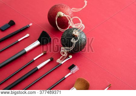 Make-up Brushes And Xmas Decoration Against Red Background, Copy Space