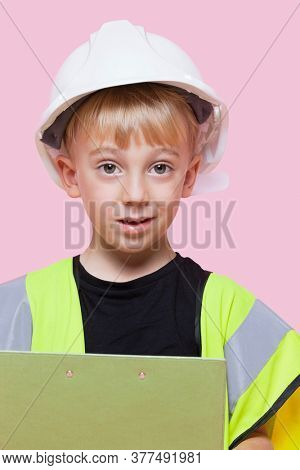 Portrait of a young boy pretending at construction worker over pink background