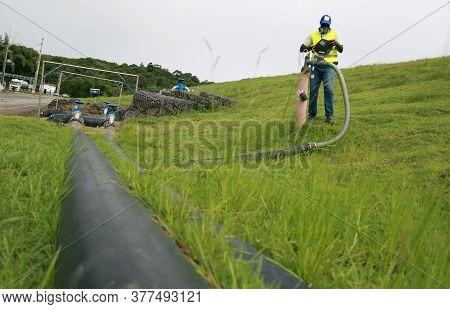 Salvador, Bahia / Brazil - July 15, 2015:  Landfill Employee Measures Methane Gas Produced On Site.