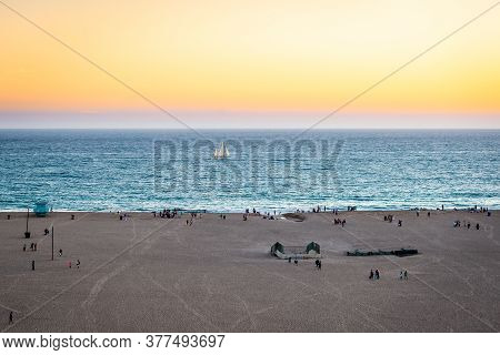View Of The Beach Of Santa Monica In The Dusk, With People Leaving The Beach And A Sailing Boat In T
