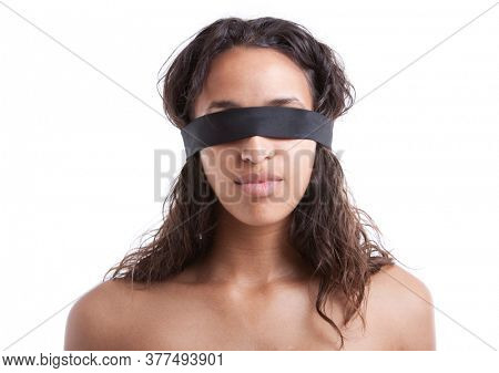 Young Mixed Race woman wearing blindfold against white background
