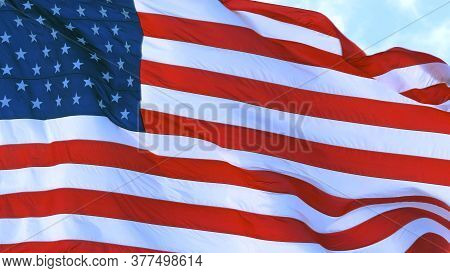 American Flag Of The Usa Flutters In The Wind Against A Clear Blue Sky On A Sunny Day. Close Up.