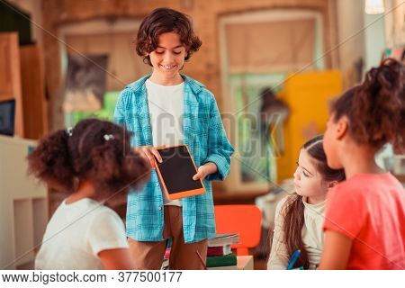 Boy Showing A Tablet To His Classmates