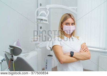 Oral Hygiene. Portrait Of Female Dentist Standing Cross Hands On Dentist Chair Background.