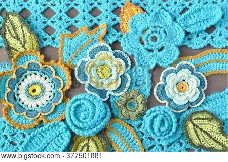 Handmade Crocheted Teal Flowers And Leaves Close Up On Crocheted Teal Pattern And Brown Background