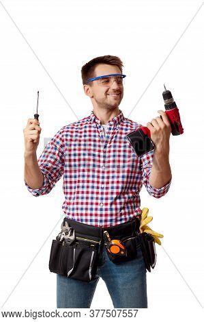 Repairman Worker Chooses Between Cordless Screwdriver And Screwdriver. Handyman Wearing Tool Belt Is