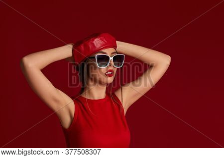 Beautiful Brunette Woman In Trendy Sunglasses, Hat And Dress Posing In Studio On Red Background.