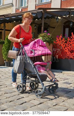 Woman Walks In The City With A Stroller, The Baby Sleeps In A Stroller In The City And Mom Goes Shop