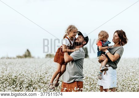 Happy Family Is Playing, Having Fun On The Field With Flowers At Sunset. Family And Love Concept. Yo