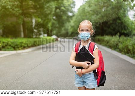 School Child Wearing Face Mask During Coronavirus Pandemic Outbreak. Blonde Girl Going Back To Schoo