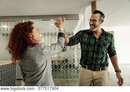 Two Ecstatic Businesspeople Celebrating And High-fiving Each Other While Working Together In A Moder