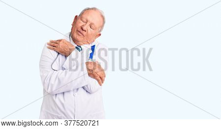 Senior handsome grey-haired man wearing doctor coat and stethoscope hugging oneself happy and positive, smiling confident. self love and self care
