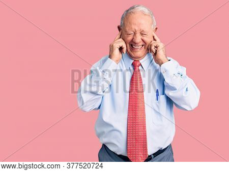 Senior handsome grey-haired man wearing elegant tie and shirt covering ears with fingers with annoyed expression for the noise of loud music. deaf concept.