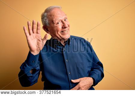 Grey haired senior man wearing casual blue shirt standing over yellow background Waiving saying hello happy and smiling, friendly welcome gesture