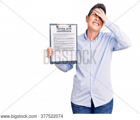Young woman with short hair holding clipboard with terms and conditions document stressed and frustrated with hand on head, surprised and angry face