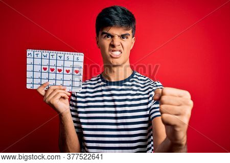 Young handsome man holding calendar with hearts over isolated red background annoyed and frustrated shouting with anger, crazy and yelling with raised hand, anger concept