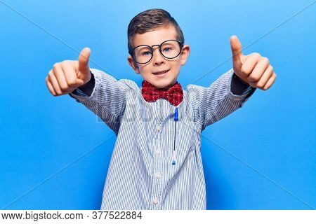 Cute blond kid wearing nerd bow tie and glasses approving doing positive gesture with hand, thumbs up smiling and happy for success. winner gesture.