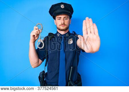 Young caucasian man wearing police uniform holding handcuffs with open hand doing stop sign with serious and confident expression, defense gesture