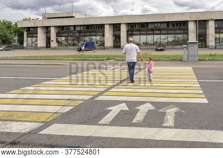 07 19 2020 Russia, Moscow, Victory Park. Dad Leads Daughter Along The Crosswalk