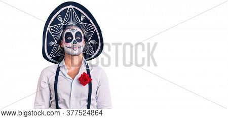 Man wearing day of the dead costume over background puffing cheeks with funny face. mouth inflated with air, crazy expression.