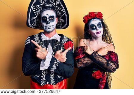 Young couple wearing mexican day of the dead costume over yellow pointing to both sides with fingers, different direction disagree