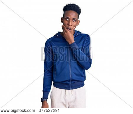 Young african american man wearing sportswear looking fascinated with disbelief, surprise and amazed expression with hands on chin