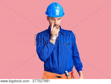 Young handsome man wearing worker uniform and hardhat swearing with hand on chest and open palm, making a loyalty promise oath