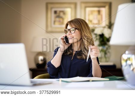 Shot Happy Businesswoman Sitting At Desk Behind Her Laptop And Talking With Somebody On Her Mobile P