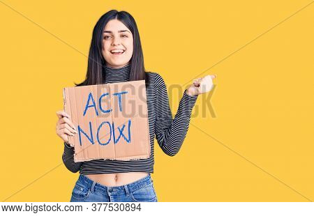 Young beautiful girl holding act now cardboard banner screaming proud, celebrating victory and success very excited with raised arms
