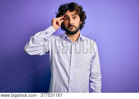Young handsome business man with beard wearing shirt standing over purple background worried and stressed about a problem with hand on forehead, nervous and anxious for crisis