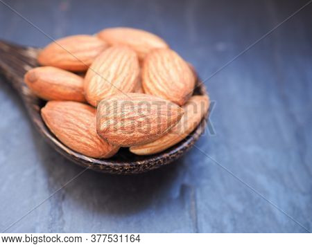 Colse Up Organic Almonds Seeds In A Wooden Spoon On Black Stone Background. Copy Space.