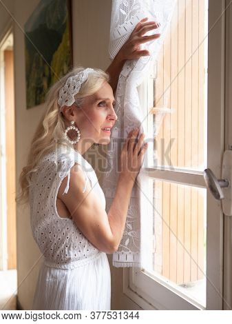 Vertical Portrait Of A Beautiful And Happy Mature Woman Standing And Looking Through The Window