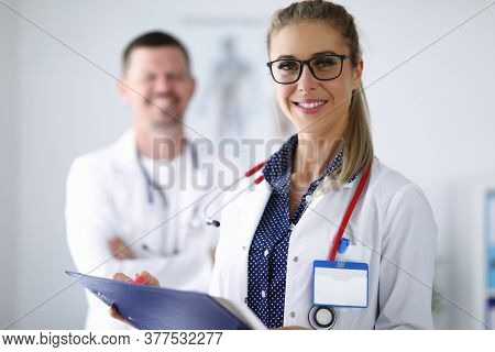 Female Doctor Smiling And Holding Clipboard From Behind Her Colleague Is Standing. Medina Services O