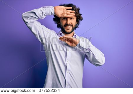 Young handsome business man with beard wearing shirt standing over purple background Smiling cheerful playing peek a boo with hands showing face. Surprised and exited