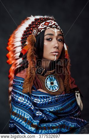 Portrait Of A Beautiful American Indian Woman In Ethnical Costume And Traditional Make Up. Studio Po
