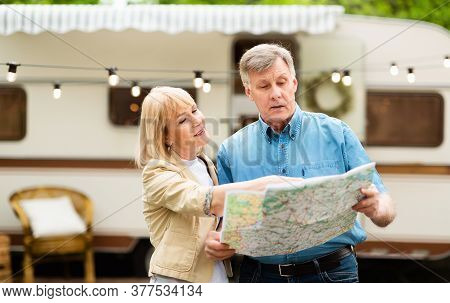 Mature Couple Looking At Map And Trying To Find Direction Near Their Trailer At Campground, Copy Spa