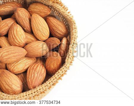 Organic Almonds Seed In Sackcloth Bag Isolated On A White Background. Top View.
