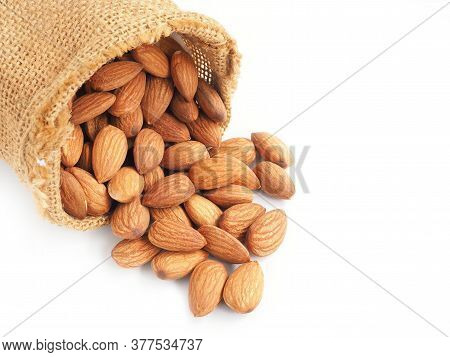 Close Up Almonds Seed In Sackcloth Bag Isolated On A White Background.
