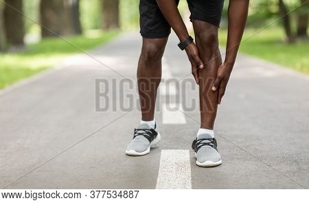 Closeup Of Black Sportsman Touching His Aching Leg While Jogging Outdoors, Empty Space