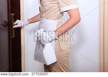 Room Service In The Hotel. A Maid In Uniform Knocks On The Door. Hospitality And Cleaning Concept.pl