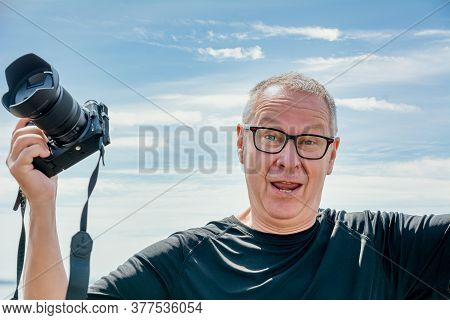 A Middle-aged Man, In His 50th, Holds Up A Camera, Looks Straight Into The Camera, And Looks Happy.