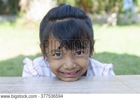 Asian Little Girl Sit Smile And Placed His Chin On A Wooden Table In The Lawn.