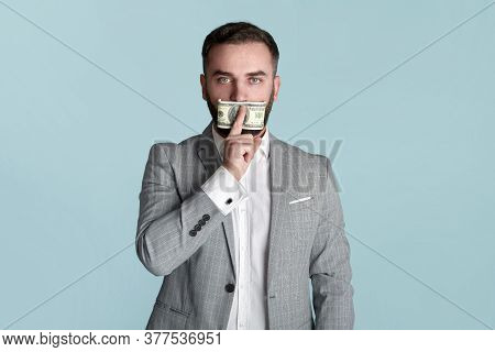 Silenced By Money Concept. Young Businessman Covering His Mouth With Hundred Dollar Bill Over Blue B