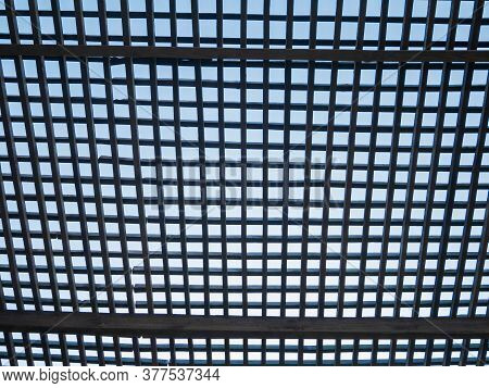 Wooden Square Timber Lattice Fence On A Blue Sky Background. Mesh Canopy Partly Cloudy Skies Beyond.