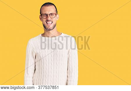 Young handsome man wearing casual clothes and glasses winking looking at the camera with sexy expression, cheerful and happy face.