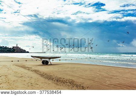 Empty Mediterranean Beach With Boat And Birds Near Old Yaffa In Tel Aviv, Israel.
