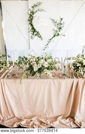 Close Up Of Presidium Of The Newlyweds At The Wedding. Table For The Bride And Groom With Flowers An