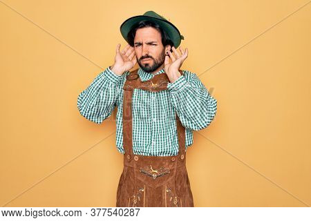 Young handsome man wearing tratidional german octoberfest custome for Germany festival Trying to hear both hands on ear gesture, curious for gossip. Hearing problem, deaf
