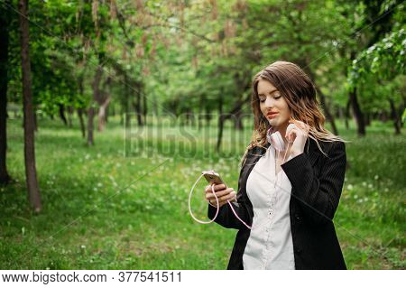 Language Learning, Online Study Concept. Young Girl In Headphones And With A Smartphone Learns A For