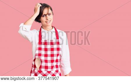 Beautiful young woman with short hair wearing professional cook apron confuse and wonder about question. uncertain with doubt, thinking with hand on head. pensive concept.